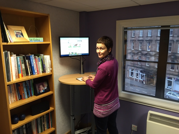 Lyndsay using Roger's standing desk (tip-toes required!)